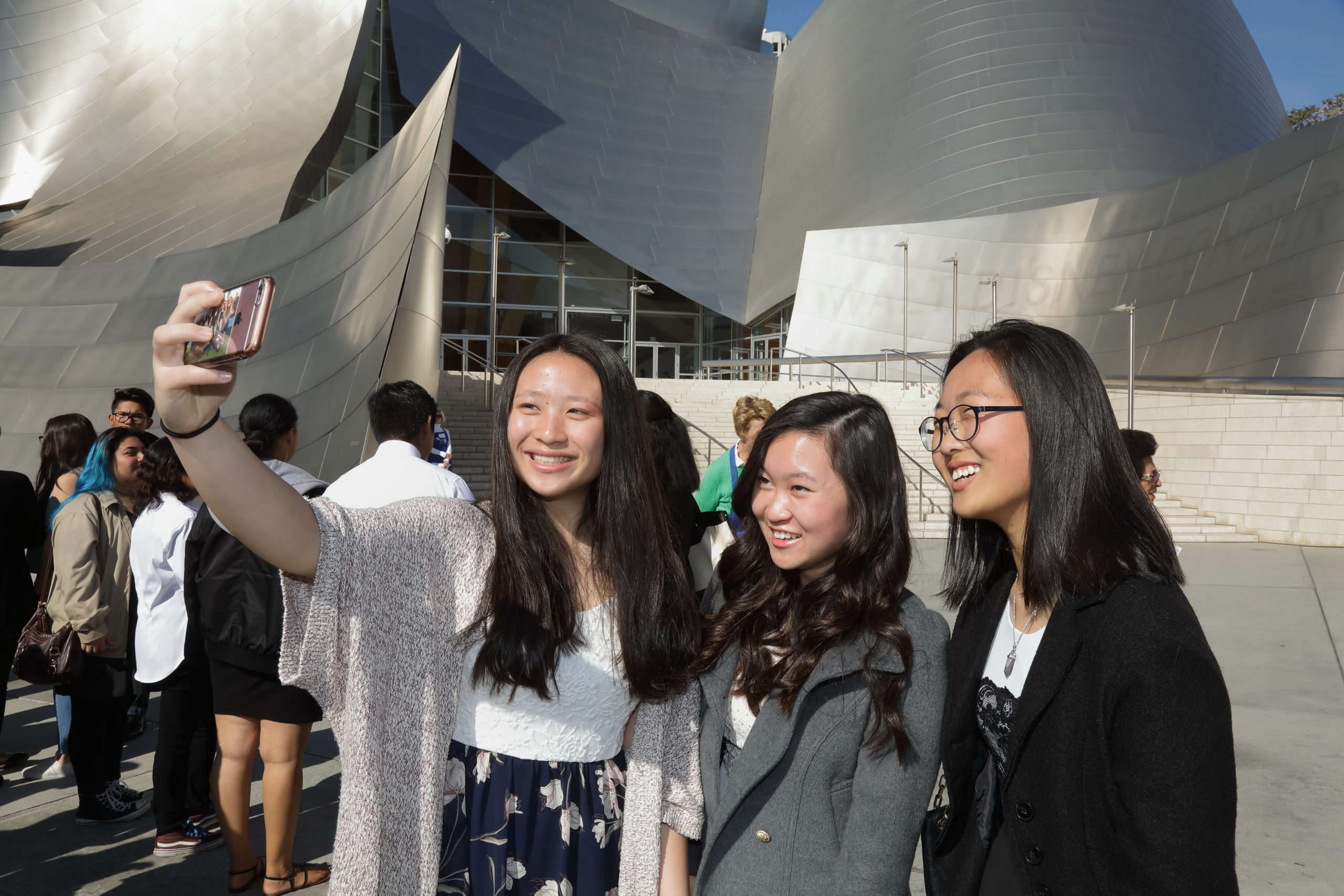 Students taking selfies in front of Disney Hall