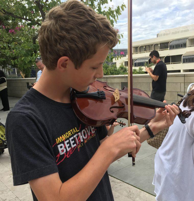 Teen playing violin outside Disney Hall
