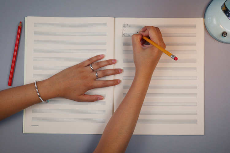 Arms and Hands Showing Writing on Music Score Paper